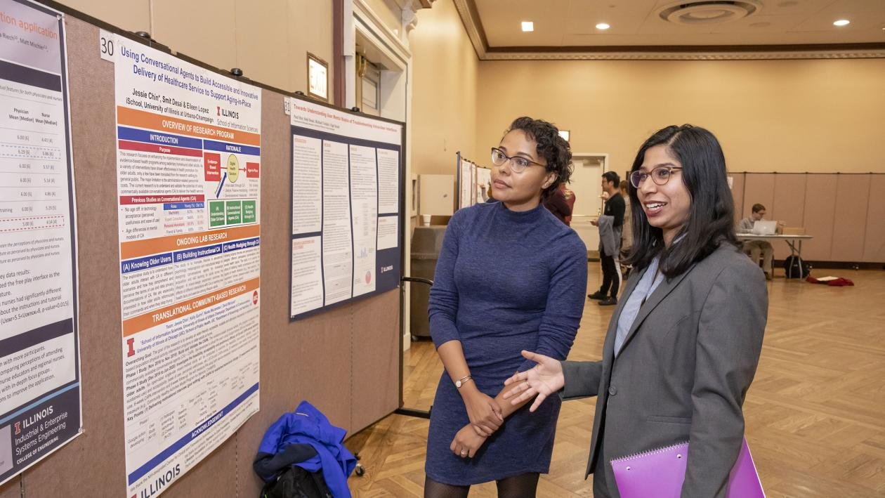 two students discussing poster at research showcase